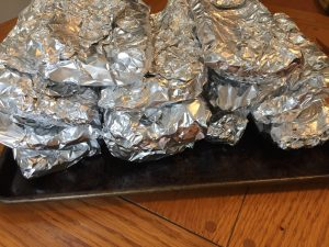 Smoked baby back ribs wrapped in tinfoil and wet rubbed