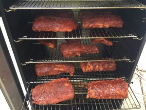 Baby back ribs, cut in half, loaded into the smoker.